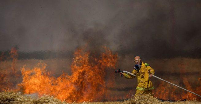 Israelische Feuerwehrleute löschen ein brennendes Weizenfeld an der Grenze zu Gaza am 30. Mai 2018. Brennende Lenkdrachen aus Gaza haben das Feld in Brand gesetzt.