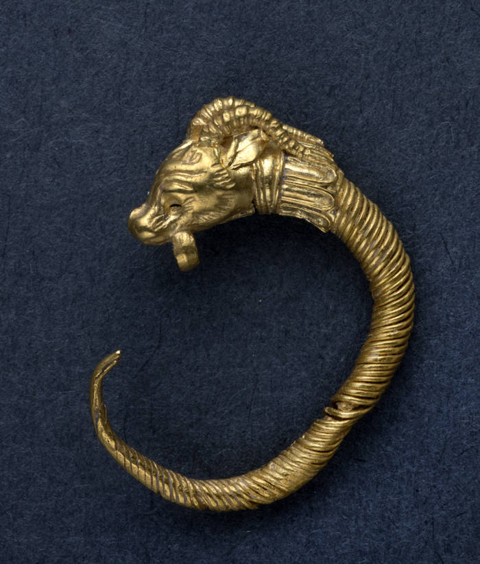 Das winzige, filigrane Goldstück zeigt den Kopf eines gehörnten Tieres.